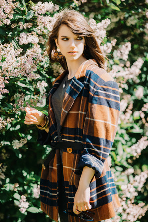A portrait of a young fashionable woman in the park. Beauty, fashion. Reklamní fotografie