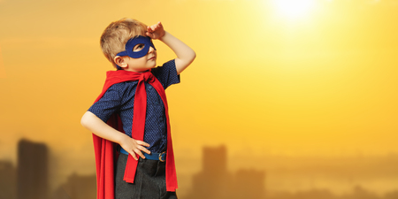 A portrait of a serious young boy posing in the costume of superhero. Kids development and education concept.