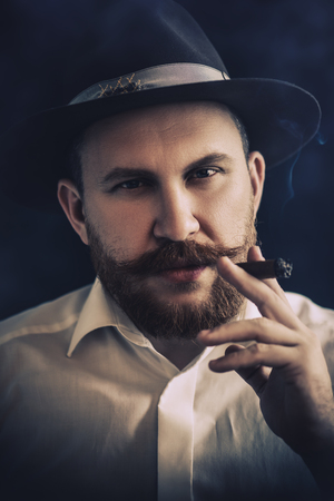 A close up portrait of a thoughtful man with a cigar posing in the studio over the black background. Mens beauty, fashion, style.