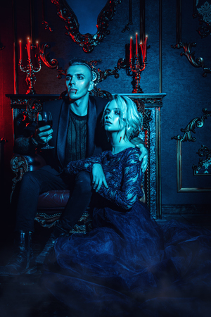 A beautiful couple of vampires is in a dark vintage room. Classic style. Beauty, fashion.