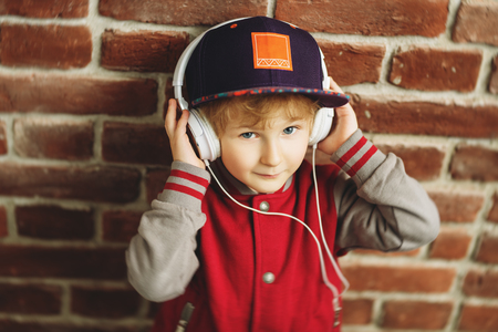 A portrait of a young schoolboy posing in the studio over the brick wall and listening to music in the headphones. Kids casual fashion, education. Banco de Imagens