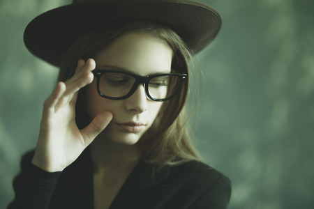 A portrait of a young dark-haired girl in a hat posing in the studio. Beauty, optics, fashion. Stock Photo
