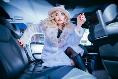 Un portrait d'une magnifique dame blonde posant dans une voiture. Voiture, mode, beauté, poussin. Banque d'images