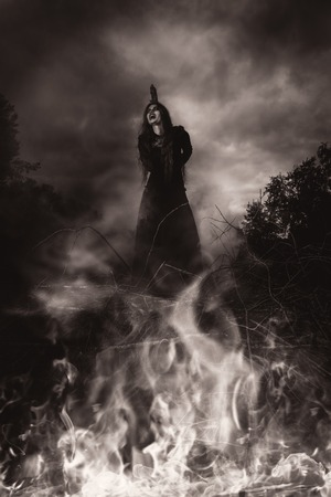 A portrait of an angry witch tied for incineration. Magic, dark force, spell. 写真素材 - 129441838