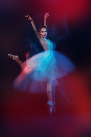 A full length portrait of a refined female ballet dancer posing in the studio over the black background. Talent, fashion for ballet dancers.