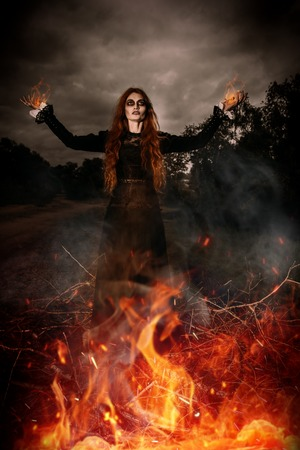 A portrait of an angry witch near the fire. Magic, dark force, spell.