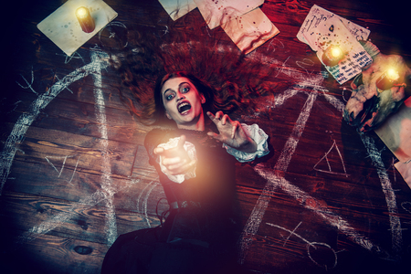 A portrait of a scary witch in the wooden house. Magic, dark force, spell.