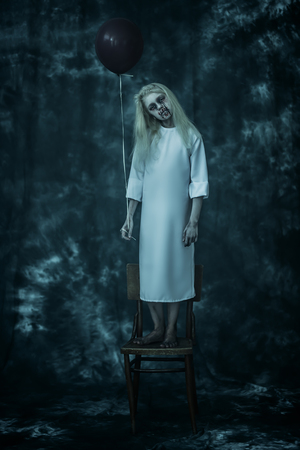 A full length portrait of a scary pale girl from a horror film with a baloon on the chair. Zombie, halloween. 写真素材 - 129442008