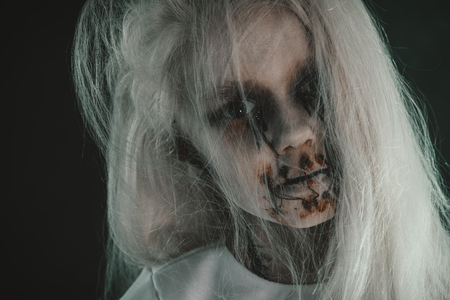 A close up portrait of a scary pale girl from horror film. Zombie, halloween. 写真素材