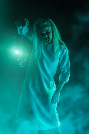 A portrait of a scary pale girl from a horror film with a lantern. Zombie, halloween. 写真素材