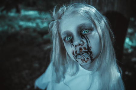 A portrait of a scary pale girl from a horror film in the forest. Zombie, halloween. 写真素材 - 129442618