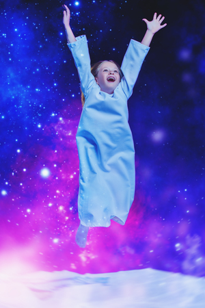 A portrait of a young pretty emotional girl jumping in bed. Relax, pajamas.
