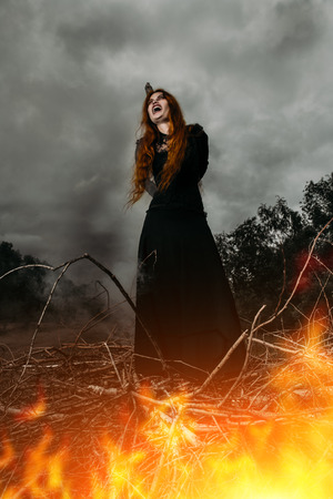 A portrait of an angry witch tied for incineration. Magic, dark force, spell.