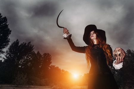 A portrait of an angry witch with a skull and a hook near the forest. Magic, dark force, spell. 写真素材 - 129443172