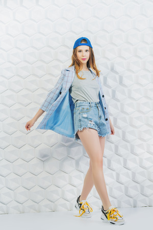 A full length portrait of a stylish bright fashionable girl posing in the studio over the white background. Summer casual fashion.