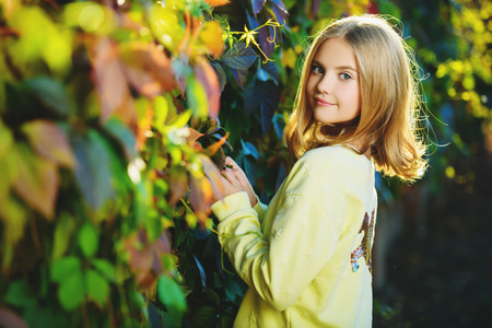 A portrait of a pretty young girl outside in autumn. Autumn fashion, beauty.