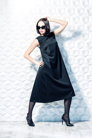 A full length portrait of a beautiful woman wearing a black dress and sunglasses. Fashion, style. 스톡 콘텐츠