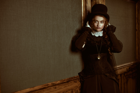 Beautiful Victorian woman in black dress and top hat stands in vintage interior. Steampunk.