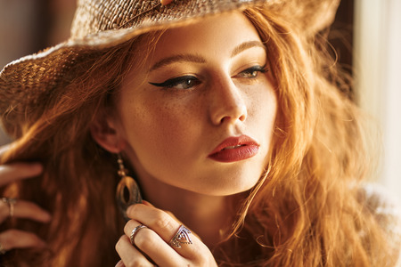 Portrait of a beautiful red-haired girl. Beauty and make-up concept. Hippie style. Bohemian style.
