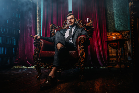 A full length portrait of a handsome mature man in a formal costume sitting in the armchair in the classic interior. Mens beauty, fashion.