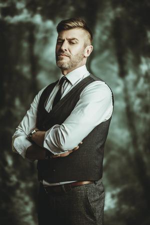A portrait of a handsome brutal mature man posing in the studio. Formal fashion for men.