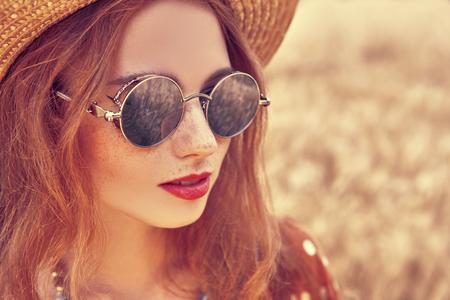 Portrait of a modern hippie girl in a wheat field. Bohemian style. 스톡 콘텐츠