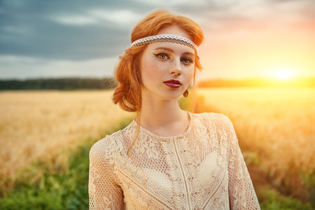 Romantic young woman with beautiful red hair walking in a golden wheat field. Beauty, fashion. Modern hippie, bohemian style.