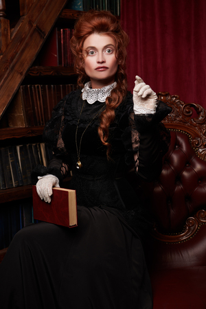 Historical reconstruction of the Victorian era. Portrait of an elegant woman in vintage  dress and hairdo reading a book in her library. Baroque era. 스톡 콘텐츠