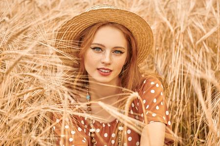 Romantic hippie girl sitting on a wheat field. Summer. Hippie, bohemian style.