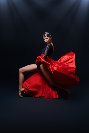 Beautiful girl professional dancer performs latino dance. Passion and expression. Black background.