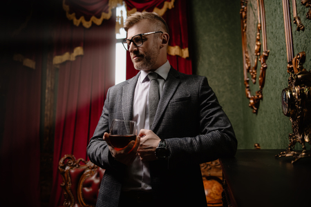 A portrait of a handsome mature man in a formal costume drinking wine. Mens beauty, fashion.