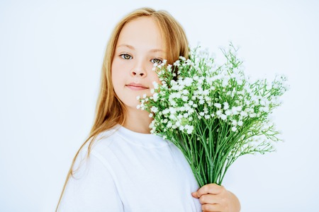 A portrait of a young pretty girl with a bouquet of flowers. Beauty, casual fashion.