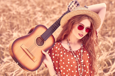 Happy hippie girl stands in a wheat field with her guitar. Spirit of freedom and independence. 스톡 콘텐츠
