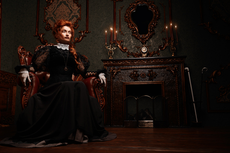 The Victorian era concept. Beautiful woman in elegant historical dress and hairstyle posing in vintage interior. Baroque. Fashion. 스톡 콘텐츠