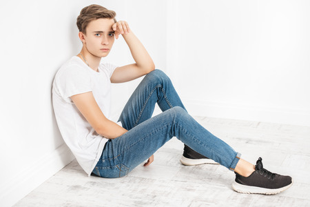 A portrait of a young goodlooking guy in a white t-shirt. Beauty of men, casual fashion.