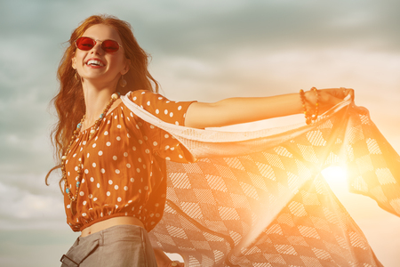 Feeling happiness. The spirit of freedom and independence. Happy laughing girl over the sky.