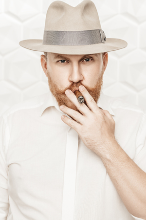 A portrait of a thoughtful man with a cigar posing in the studio over the white background. Men's beauty, fashion, style. Stock fotó