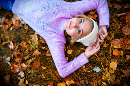 A pretty young girl is lying on the ground with golden leaves. Autumn fashion, beauty. 스톡 콘텐츠