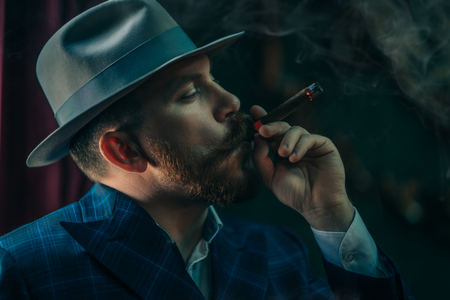 A close-up portrait of a thoughtful man with a cigar posing in the vintage interior. Mens beauty, fashion, style. 스톡 콘텐츠