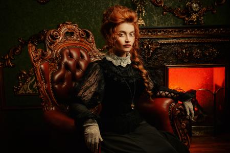 Das Konzept der viktorianischen Ära. Schöne Frau in elegantem historischem Kleid und Frisur, die im Vintage-Interieur posiert. Barock. Mode.