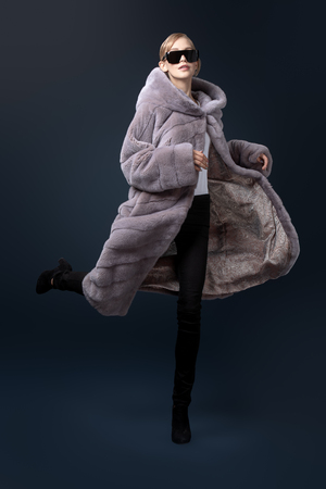 A full length portrait of a young fashionable woman in a grey mink coat. Beauty, fashion. 스톡 콘텐츠