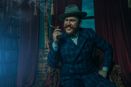 A portrait of a thoughtful man with a cigar posing in the vintage interior. Mens beauty, fashion, style. 스톡 콘텐츠