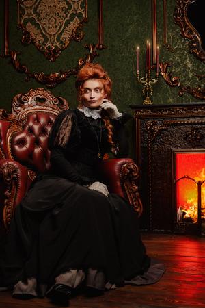 El concepto de la época victoriana. Hermosa mujer en elegante vestido histórico y peinado posando en interior vintage. Barroco. Moda.