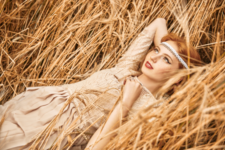 Romantic young woman with beautiful red hair lies on a wheat field. Beauty, fashion. Modern hippie, bohemian style.