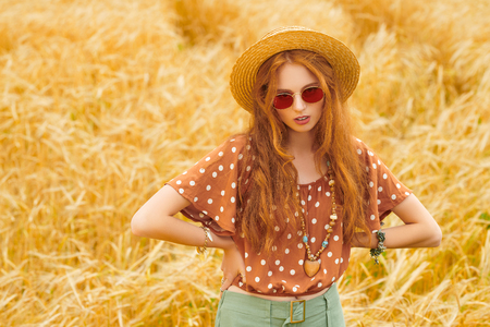 Beauty, fashion shoot. Portrait of a modern hippie girl in a wheat field. Bohemian style. Stockfoto