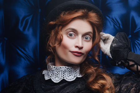 Close-up portrait of an elegant Victorian woman in black dress and top hat. Steampunk theme. The history of makeup and hairstyles.