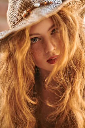 Close-up portrait of a beautiful girl with magnificent foxy hair. Beauty and hair concept. Hippie style. Bohemian style.