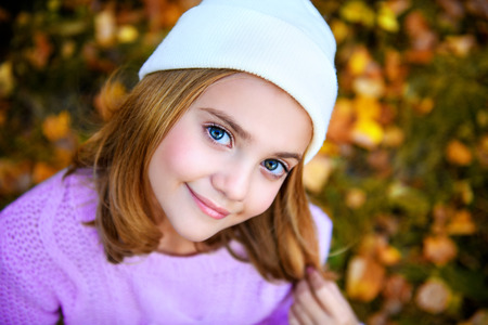 A pretty young girl is on the ground with golden leaves. Autumn fashion, beauty. 스톡 콘텐츠