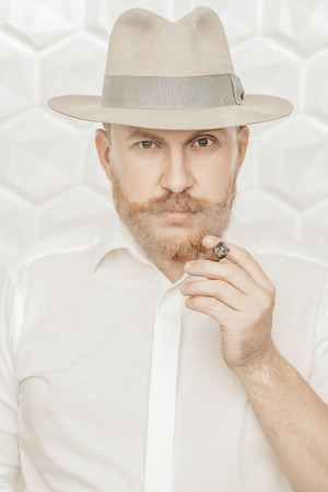 A portrait of a thoughtful man with a cigar posing in the studio over the white background. Mens beauty, fashion, style.