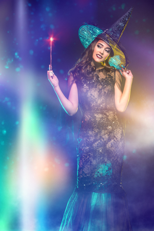A portrait of a beautiful witch in a hat holding a magic stick. Halloween. Celebration. Stock Photo